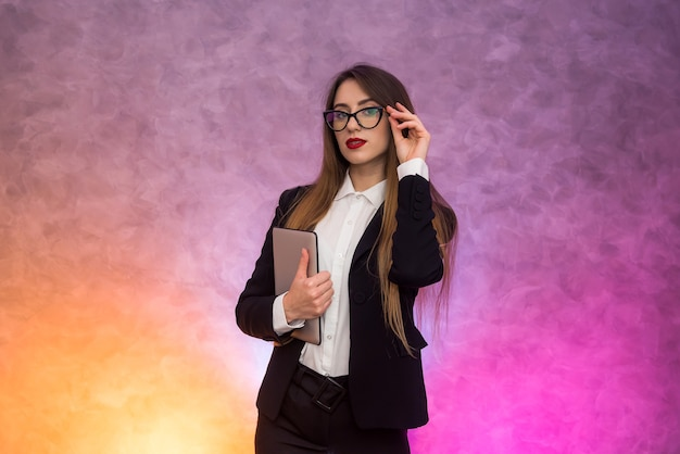 Mulher bonita de óculos usando tablet na parede abstrata