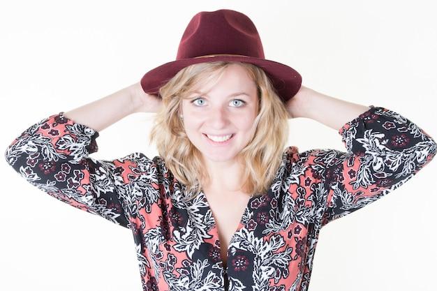 Mulher bonita de olhos azuis de cabelo loiro vestindo clotrhes preto rosa com chapéu de pé e posando