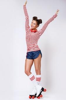 Mulher bonita de patins e com fones de ouvido vermelhos