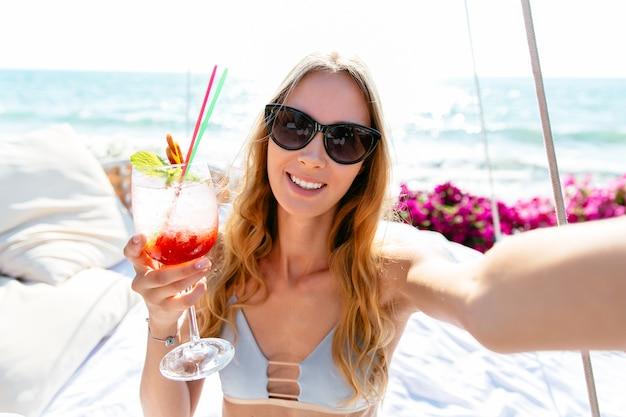 Mulher bonita de sorriso no roupa de banho e nos óculos de sol, guardando um vidro do cocktail frio.