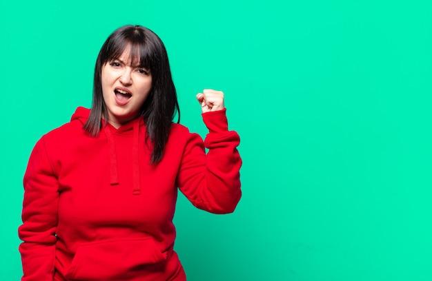 Mulher bonita de tamanho grande gritando agressivamente com uma expressão de raiva ou com os punhos cerrados celebrando o sucesso