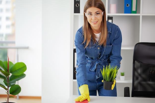 Mulher bonita de uniforme com suprimentos de limpeza no escritório.