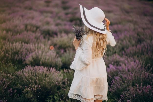 Mulher bonita de vestido branco em um campo de lavanda