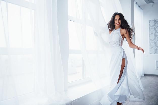 Mulher bonita de vestido branco fica na sala branca com luz do dia através das janelas