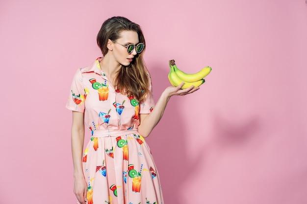 Mulher bonita de vestido colorido com friuts impressos posando com bananas