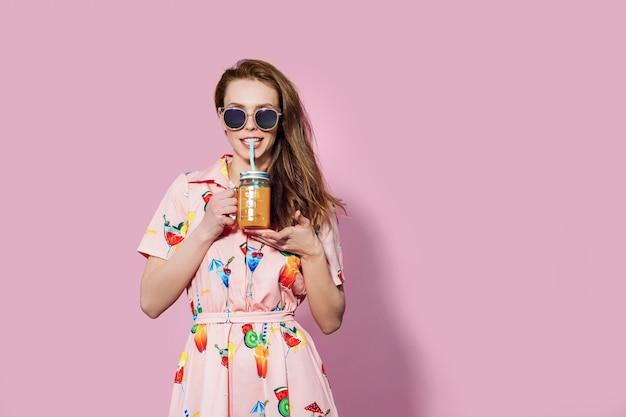 Mulher bonita de vestido colorido com friuts impressos posando com copo de suco