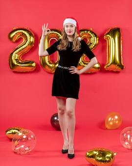 Mulher bonita de vestido preto de frente, fazendo sinal de balões em vermelho