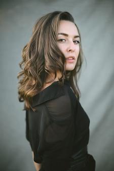 Mulher bonita de vestido preto de pé e olhando.