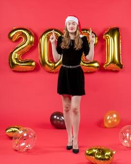 Mulher bonita de vestido preto desejando balões no vermelho