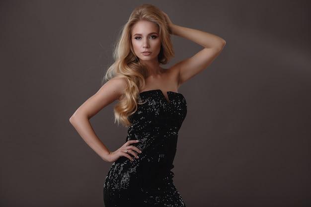 Mulher bonita de vestido preto em estúdio