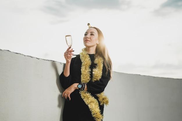 Mulher bonita de vestido preto, segurando uma taça de champanhe