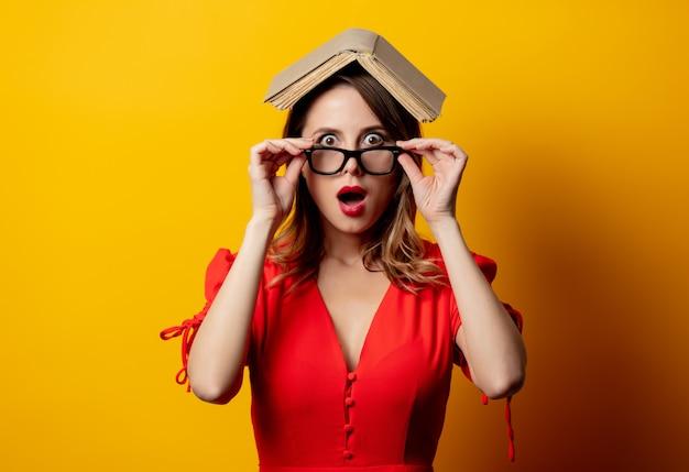 Mulher bonita de vestido vermelho com livro na parede amarela
