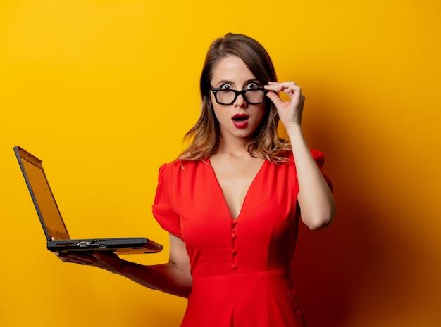 Mulher bonita de vestido vermelho com o computador portátil na parede amarela