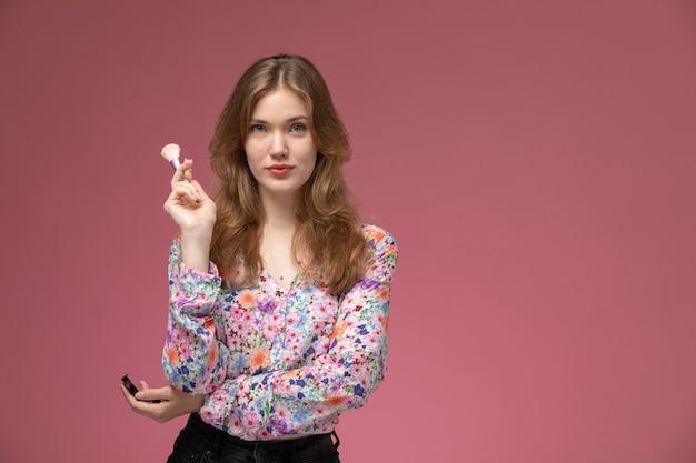 Mulher bonita de vista frontal posando com seu pincel de pó cosmético