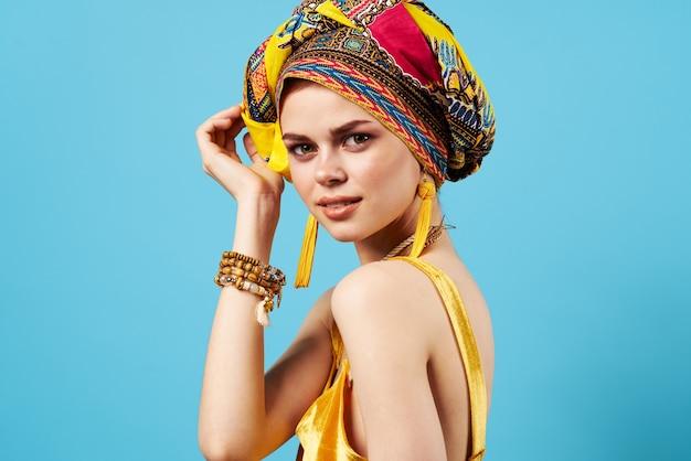 Mulher bonita decoração multicolorido lenço na cabeça etnia fundo azul. foto de alta qualidade