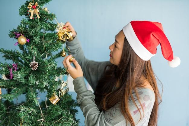 Mulher bonita decorar sinos na árvore de natal