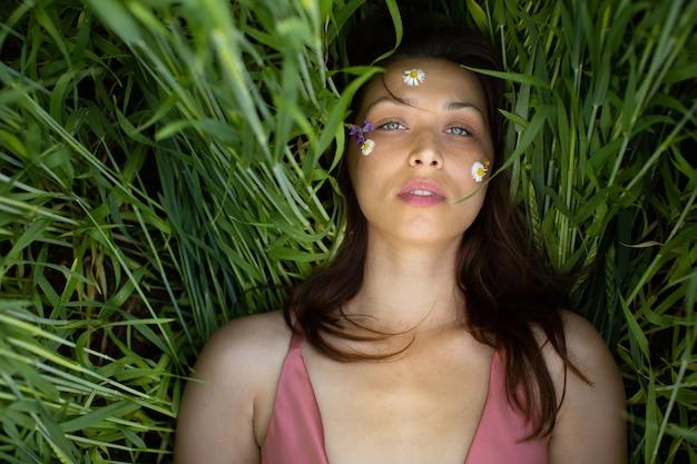 Mulher bonita deitada em um campo de grãos com flores silvestres e margaridas no rosto