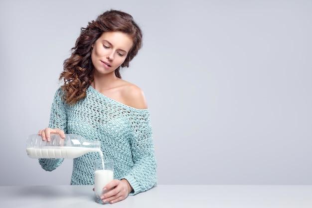 Mulher bonita derramar leite no copo