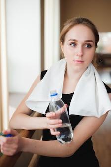 Mulher bonita descansar segurando a garrafa de água após executar a esteira. conceito de esporte de saúde.