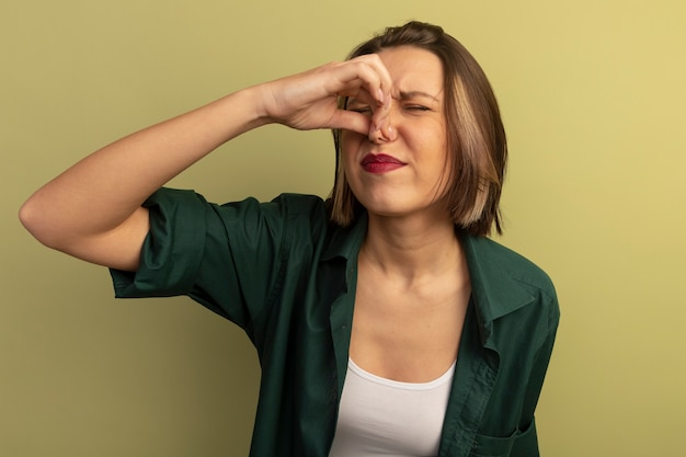 Mulher bonita descontente fechando nariz isolado na parede verde oliva