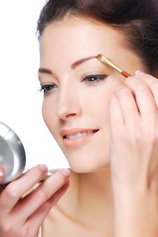 Mulher bonita desenhando sobrancelhas de beleza usando uma escova cosmética