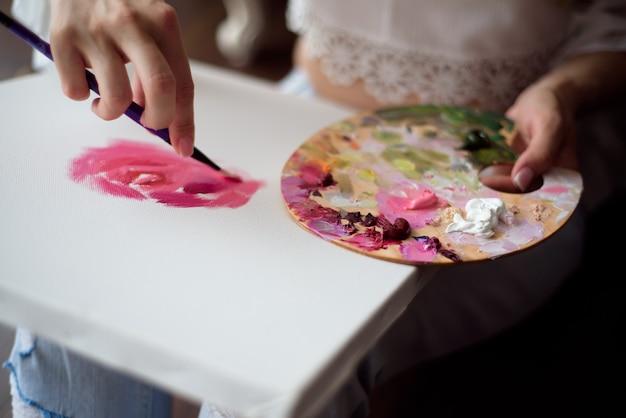 Mulher bonita desenhando sua imagem em uma tela com tintas a óleo em casa Foto Premium
