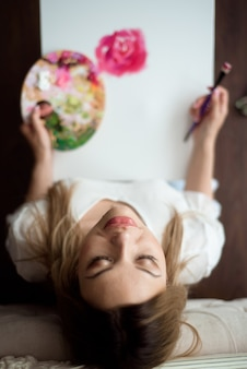 Mulher bonita desenhando sua imagem em uma tela com tintas a óleo em casa