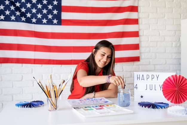 Mulher bonita desenhando uma ilustração em aquarela para o dia da independência dos eua. foco seletivo foco no primeiro plano feliz 4 de julho, o texto na mesa de luz
