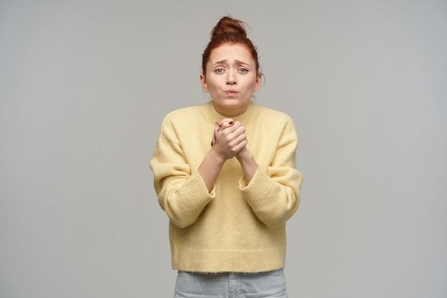 Mulher bonita, desesperada garota com cabelo ruivo preso em um coque. vestindo jeans e suéter amarelo pastel. mantenha os braços dela juntos, implorando. isolado sobre parede cinza