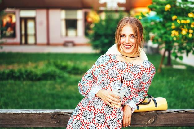 Mulher bonita, desfrutando de bebida gelada ao ar livre na rua