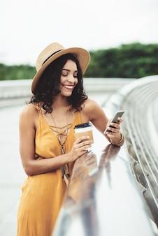 Mulher bonita, desfrutando de café e mídias sociais ao ar livre