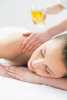 Mulher bonita, desfrutando de massagem com óleo