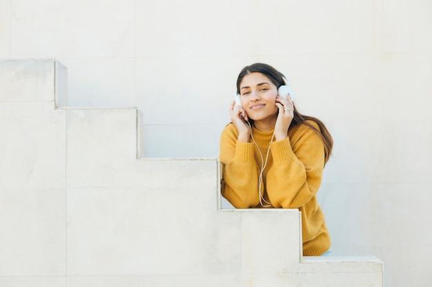 Mulher bonita, desfrutando de ouvir música em fones de ouvido, olhando para a câmera
