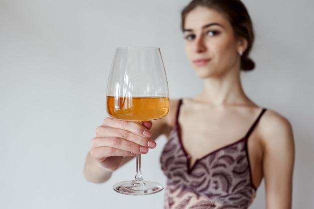 Mulher bonita, desfrutando de um copo de vinho branco.