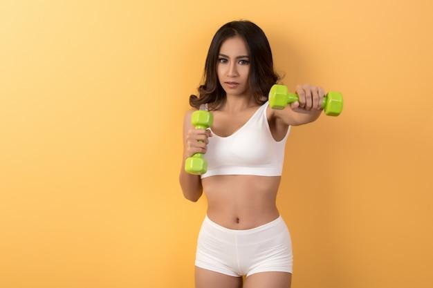 Mulher bonita desportiva, exercício com halteres
