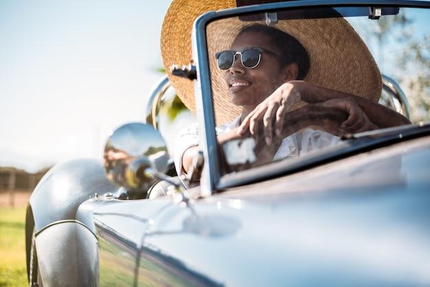 Mulher bonita, dirigindo um carro conversível antigo