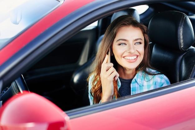 Mulher bonita dirigindo um carro vermelho, falar enquanto dirige. olhando para fora, sorrindo e falando ao telefone. cabeça e ombros, comprando carro novo