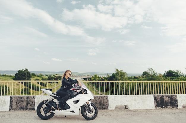 Mulher bonita, dirigindo uma moto em uma estrada