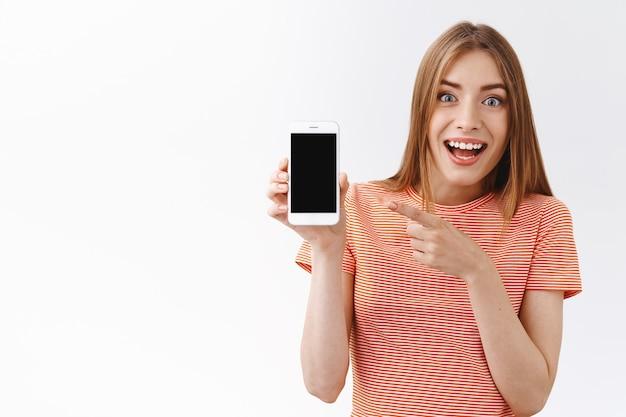 Mulher bonita, divertida e animada, em uma camiseta listrada, sorrindo com entusiasmo, segurando o smartphone apontando para a tela do celular, mostrando preços incríveis para ingressos online, fundo branco em pé