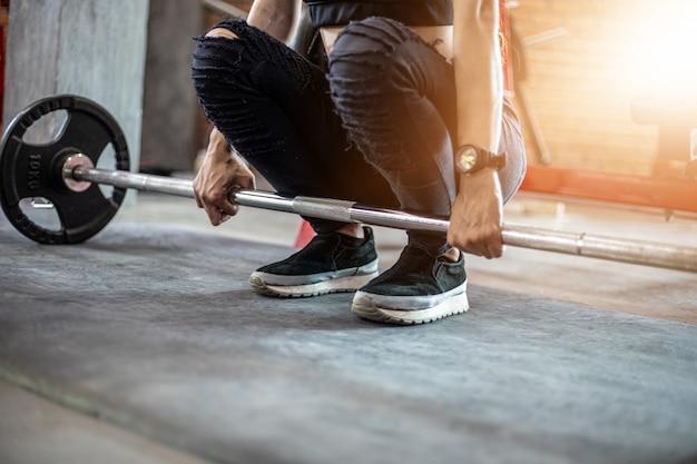 Mulher bonita do ajuste muscular que exercita os músculos do edifício e mulher da aptidão que faz exercícios no gym. fitness - estilo de vida saudável