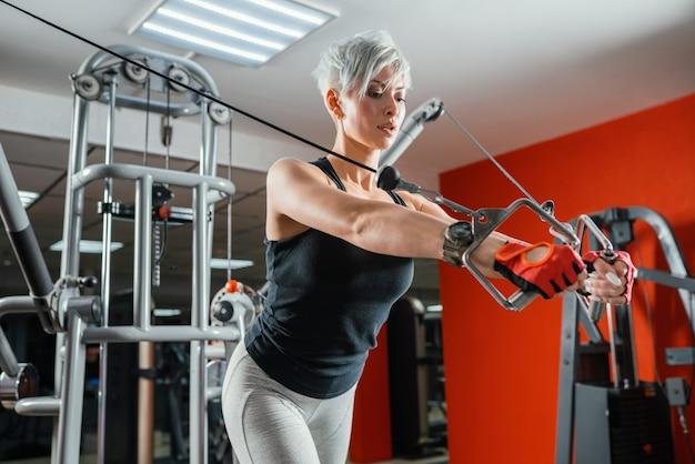 Mulher bonita do ajuste muscular que exercita os músculos do edifício