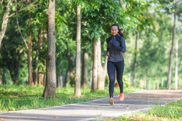 Mulher bonita do esporte no sportswear que corre no parque. estilo de vida saudável e conceito de esporte.