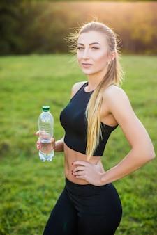 Mulher bonita do esporte usando um top e tênis em uma corrida matinal bebe água de uma garrafa