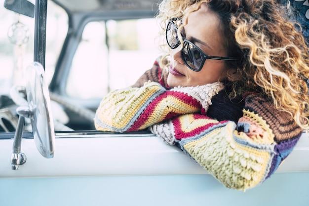 Mulher bonita do lado de fora da janela de seu carro furgão azul