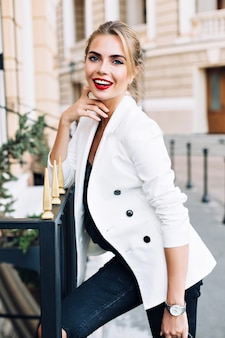 Mulher bonita do retrato encostado no muro na rua. ela está sorrindo para a câmera.