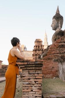 Mulher bonita do turista europeu que sightseeing os templos históricos em sukhothai, a cidade antiga com herança budista no nordeste na tailândia.
