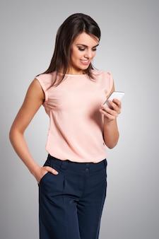Mulher bonita durante o uso de telefone celular contemporâneo