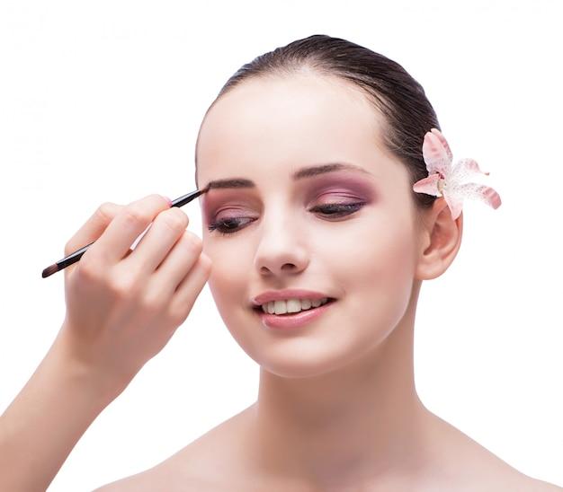Mulher bonita durante sessão de maquiagem cosméticos isolada no whi