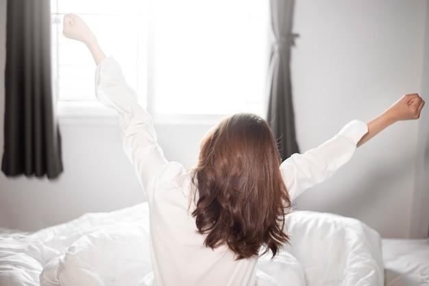 Mulher bonita é acordar na cama de manhã