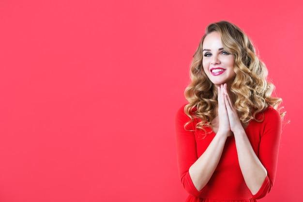 Mulher bonita e alegre com cabelo brilhante em um vestido vermelho. isolado.